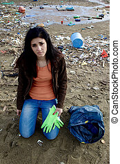 Young ecologist sad about dirty beach - Young woman trying...