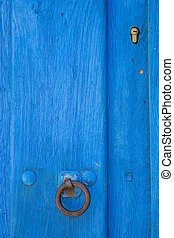 Old run-down blue painted wooden door and lock - Closeup of...