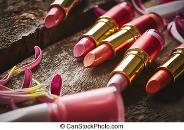 Lipsticks with nail polish and flower petals on wooden...