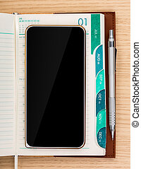 Modern mobile phone and Year business project planner book with