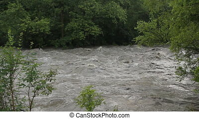 Flood river viewed from riverbank - Rough, turbulent water...