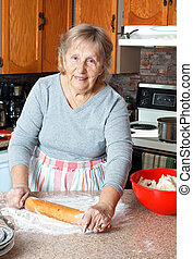 Grandma making pies - Senior woman or grandma rolling dough...
