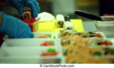 Chef dips sushi in red fish caviar - View of chef dips sushi...