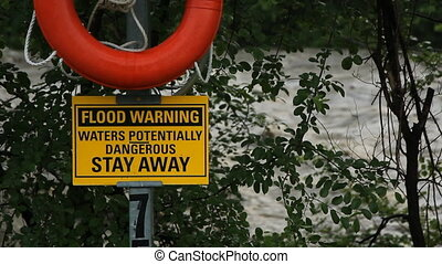 Flood warning. - Flood warning sign with river in...
