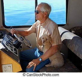 Afloat in a houseboat - Man sits at the steering wheel of a...