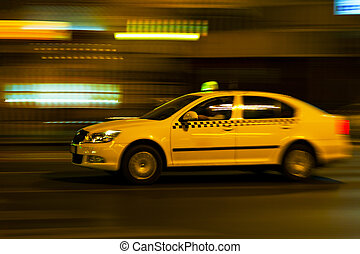 yellow taxi moves on the night city street
