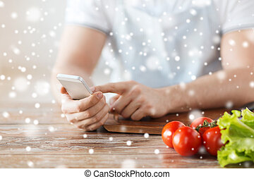 closeup of man reading recipe from smartphone - cooking,...