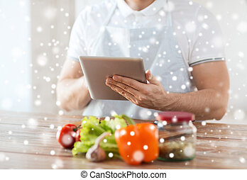 closeup of man reading recipe from tablet pc - cooking,...