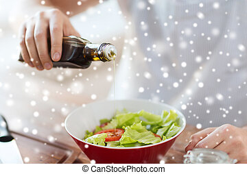 close up of hands flavoring salad with olive oil - cooking,...