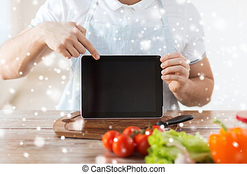 closeup of man showing tablet pc screen in kitchen -...