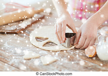 close up of woman hands making cookies from dough