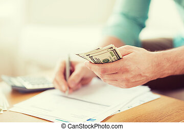 close up of man counting money and making notes - savings,...