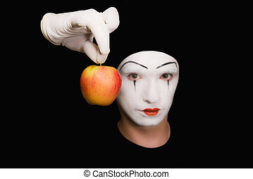 Portrait of  Mime with red apple on black background