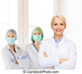 smiling female doctor with group of medics - healthcare and...