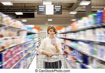 woman with shopping list pushing cart looking at goods in...