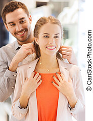 couple trying golden pendant on at jewelry store - sale,...