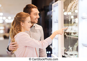 couple looking to shopping window at jewelry store - sale,...