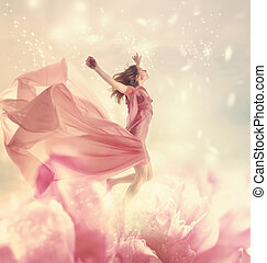 Beautiful young woman jumping on a giant flower - Beautiful...