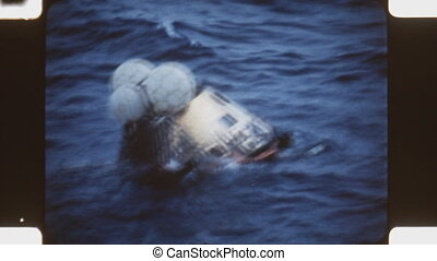 Apollo 11 module after splashdown - US Navy divers attaching...