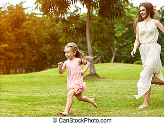 mother and daughter walking in the park, happy at sunset in...