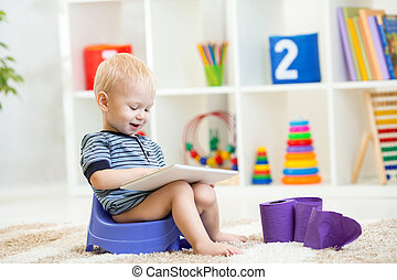 kid sitting on chamber pot playing tablet pc - smiling kid...