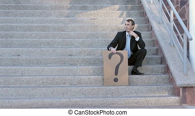 Businessman Question Mark Sign - Businessman in a suit and...