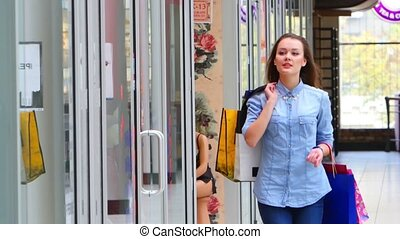 Beautiful girl with shopping bags goes on shopping center