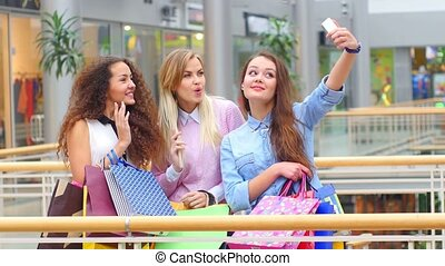 Group of happy best friends with shopping bags taking a...