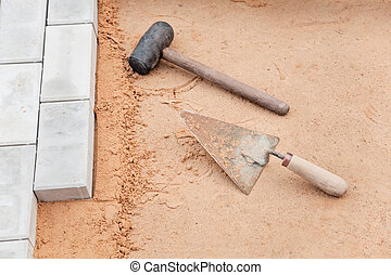 Tools of the mason on a sand - trowel and hammer