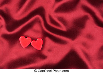 The concept of two lovers hearts lying on the red satin