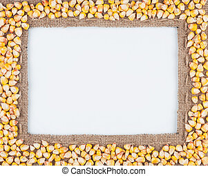 Frame of burlap and corn beans, lying on a white background