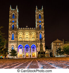 Montreal Notre Dame Basilica illuminated at night with stone...