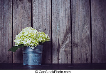 White hydrangea flower in a tin pot on an old wooden board...