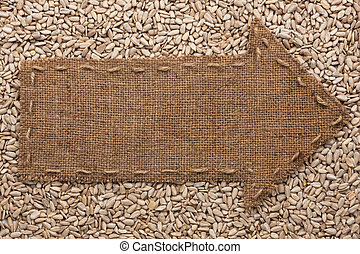 Pointer of burlap lies on sunflower seeds, with place for...