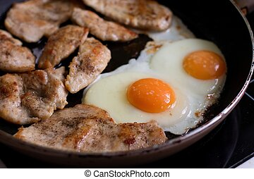 Fried eggs and chicken meat on pan - Photo of two fried eggs...