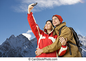 Winter sport selfie - young couple taking a selfie during...