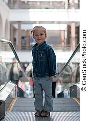 Cute little child in shopping center standing on moving staircase, escalator