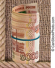 Russian rubles rolled into a tube on a background of burlap...