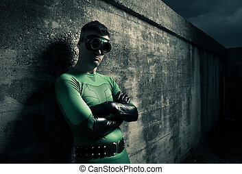Cool superhero with black leather gloves leaning to a...