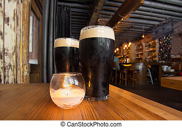 Beer - Dark beer and candle in pub setting
