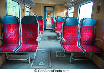 Interior of a modern train with windows and empty red seats