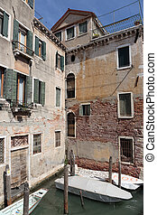 Facade of an old house on a canal in Venice, Italy