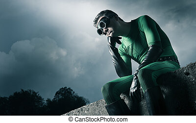 Pensive green superhero with hand on chin and cloudy...