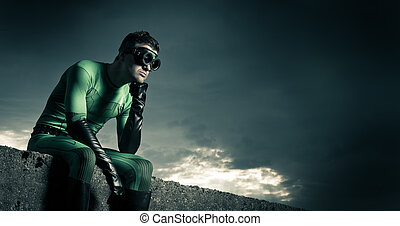 Pensive superhero against dark sky - Pensive superhero with...