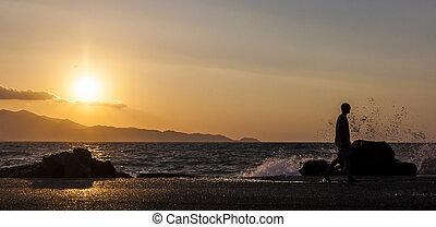 Man and waves splashing on a beautiful sunset