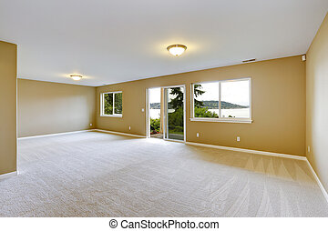 Spacious family room with clean carpet floor and exit to...