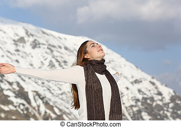 Woman breathing fresh air raising arms in winter with a...