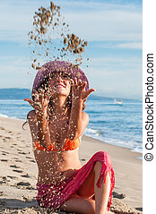 New beginning - Joyful girl sitting by the sea and throwing...