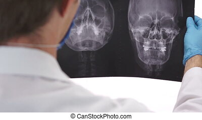 Health Care Doctor Studying an Xray - Over the shoulder shot...