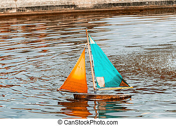 Small toy boat sailing on a lake